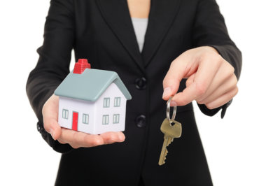 woman holding toy house and a key